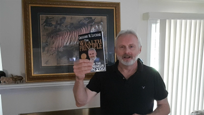 Greg Luchak displaying his book The Wealth Principle